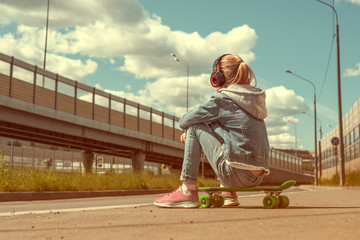 Teen on skateboard in jeans clothes, on the background of industrial