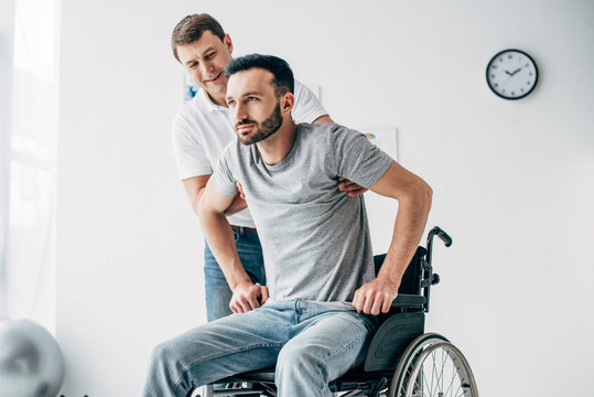 Physiotherapist helping handicapped man in Wheelchair during recovery in hospital