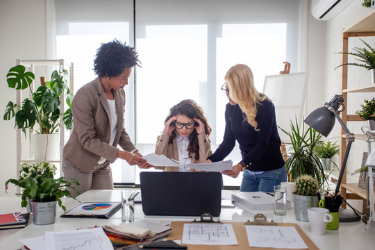 Three multiethnic woman at the office try to solve problems at work