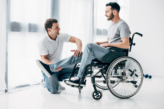 smiling Physiotherapist massaging leg of handicapped man in wheelchair