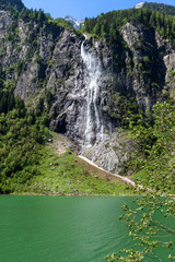 Waterfall flows over granite roocks in the mountains, Stillup Lake,  Austria, Tyrol, Zillertal