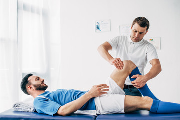 Physiotherapist massaging leg of football player lying on massage table in hospital
