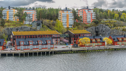 Vintage wooden renovated storehouses painted in traditional falun red on Nacka strand, suburb of Stockholm, in front of modern residential buildings.