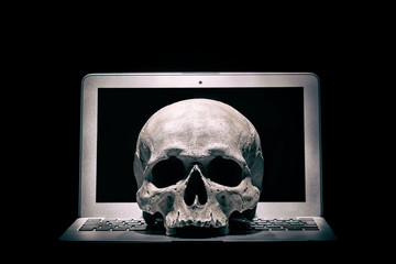 Cybercrime or hacking concept. Laptop in dark room under beam of light with a skull. Idea of virus or worm program cyber attack.
