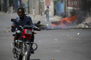 A man drives a motorbike next to a burning barricade during a demonstration on the second day of a strike in Port-au-Prince