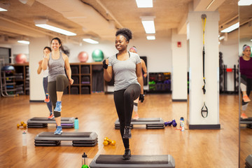 Smiling female athletes stepping on aerobic steps in gym