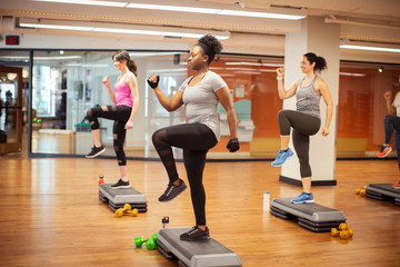 Side view of confident female athletes exercising on aerobic steps in gym
