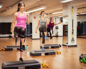 Smiling female athletes with trainer exercising on aerobic steps in gym