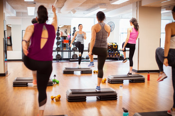 Trainer with female athletes exercising on aerobic steps in gym