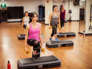 Full length of confident female athletes with dumbbells exercising on aerobic steps in gym