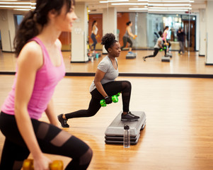 Side view of female athletes with dumbbells exercising on aerobic steps in gym