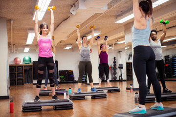 Rear view of female trainer and athletes exercising with dumbbells while standing on aerobic steps in gym