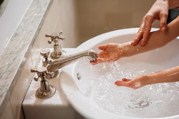 Cropped image of mother washing daughter's hands in sink at home