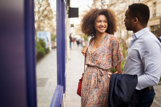 Happy couple talking while standing by store in city