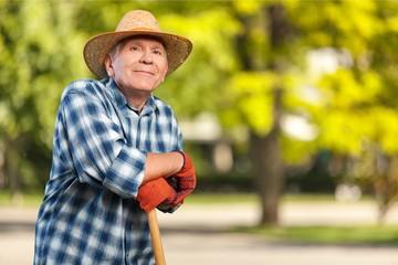 Happy senior man in hat at work on field