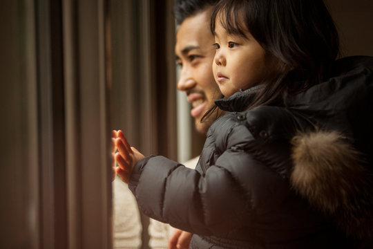 Father and cute daughter looking through window at home during winter