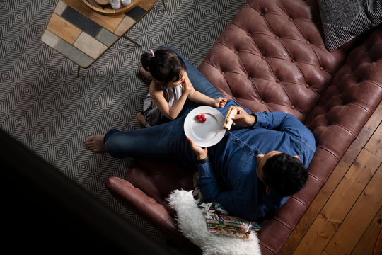High angle view of father and daughter eating food on sofa