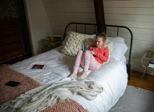 High angle view of girl reading book while relaxing on bed against wall at home
