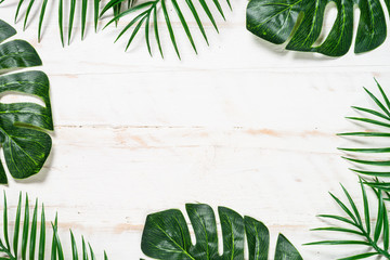 Palm leaves on white wooden background top view. Wall mural