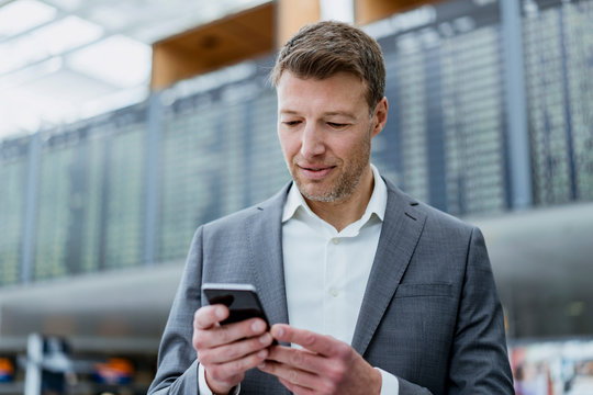 Portrait of businessman using cell phone at the airport