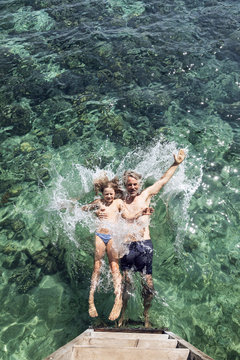 Overhead view of father and daughter falling into sea