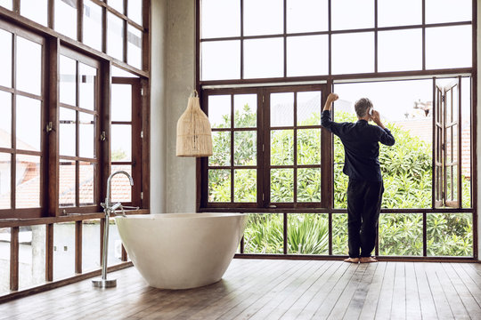 Man in bathroom on cell phone at the window in tropical surrounding