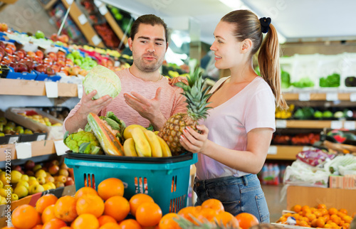 Nice Couple Standing With Full Grocery Cart Stock Photo And
