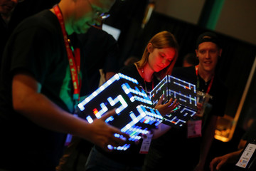 Attendees try out new gaming hardware called Pixxelcube as it makes its world debut during opening day of E3, the annual video games expo revealing the latest in gaming software and hardware in Los Angeles