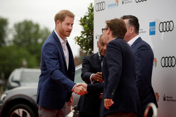 Britain's Prince Harry walks with the Managing Director of Audi UK Andrew Doyle and the Chairman of Sentebale Johnny Hornby after arriving for a concert hosted by his charity Sentebale at Hampton Court Palace, in London