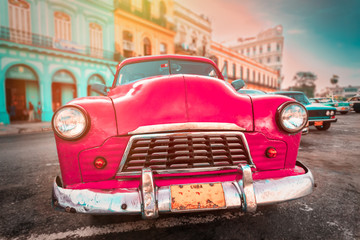 Poster Havana Antique pink car inext to colorful buildings in Old Havana