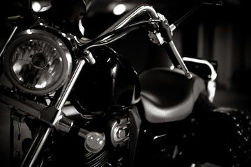 Black and white vintage photo of chopper bike details, chromed, with soft light and reflections, with side leather bags. Motorcycle wallpaper, background