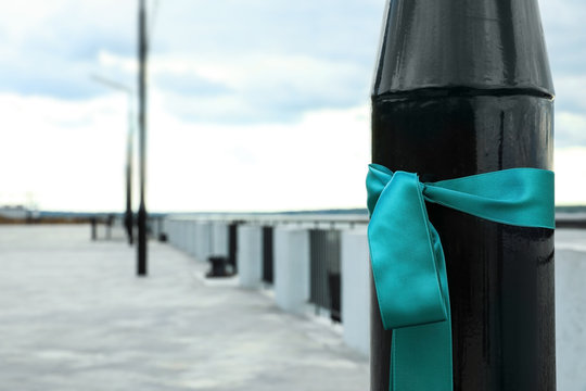 Teal ribbon tied to street lamp outdoors, space for text