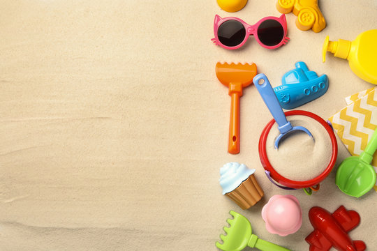 Flat lay composition with beach toys on sand. Space for text