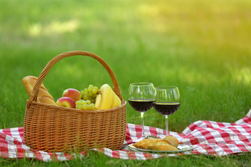 Aluminium Prints Picnic Wicker basket with food and wine on blanket in park, space for text. Summer picnic