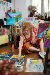 Foto op Aluminium Imagination Red-haired woman wearing orange trousers coloring on floor