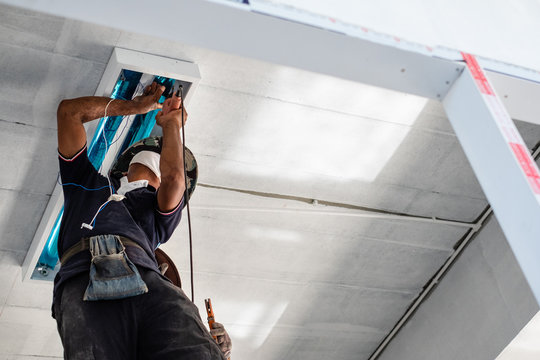 Technician is installing fluorescent bulbs on ceiling of building. Home improvement concept.