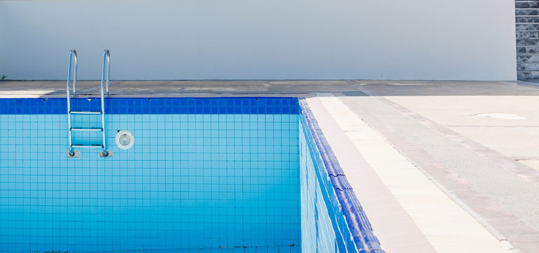 Empty dry swimming pool preparing for cleaning.