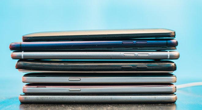 Vertical heap of many broken cell phones. Mobile phone repair concept.
