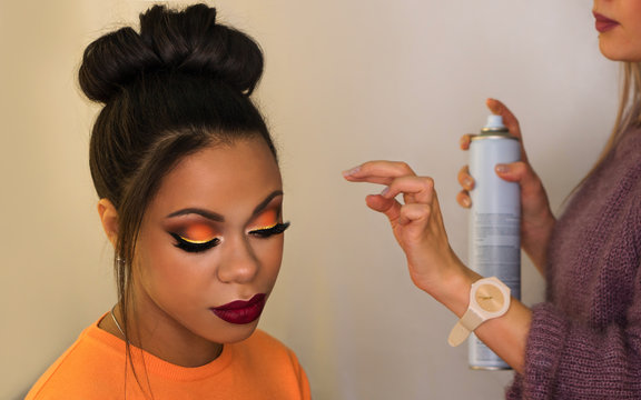 Young woman African American with perfect skin facial. Fashion luxury makeup orange-coloured shades. Long eyelashes, pouty lips. Upper bun hair. Professional hair stylist uses hairspray to fix hair. F
