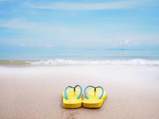 yellow sandal on beige sand summer beach background.