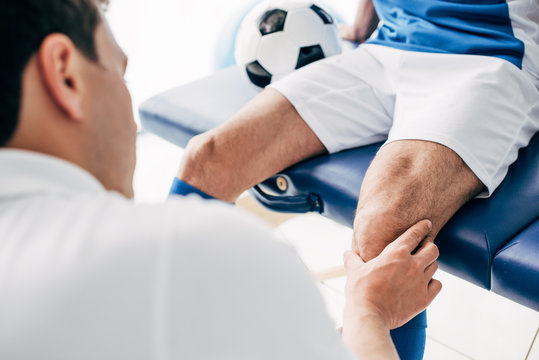 partial view of Physiotherapist massaging leg of football player in hospital