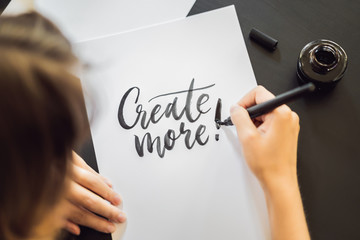 Creat more. Calligrapher Young Woman writes phrase on white paper. Inscribing ornamental decorated letters. Calligraphy, graphic design, lettering, handwriting, creation concept