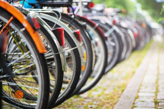 Group of bicycles in the row on parking for bikes in European city.