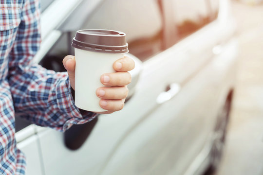 people person business man drinking paper cup coffee of hot in hand while standing car on the side before driving a vehicle in the Morning sunlight .transportation and vehicle concept.