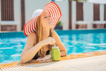 Woman with a green smoothies of spinach and banana on the background of the pool. Healthy food, healthy smoothies