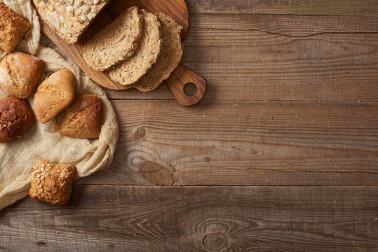 top view of fresh bread slices on chopping board and buns on cloth on wooden table
