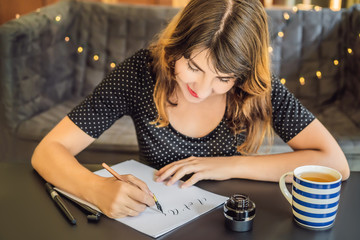 Calligrapher Young Woman writes phrase on white paper. Inscribing ornamental decorated letters. Calligraphy, graphic design, lettering, handwriting, creation concept