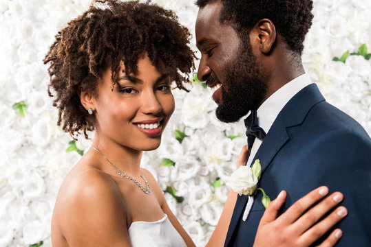 cheerful african american bride hugging handsome bridegroom near flowers