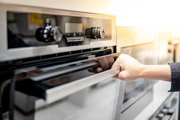 Male hand opening oven door in the kitchen showroom. Buying cooking appliance for domestic kitchen....