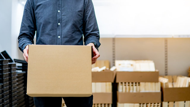 Young courier man carrying cardboard box near product shelves in warehouse. Parcel shipping service or delivery packaging concept
